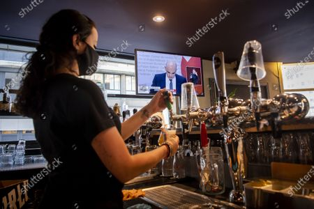 A waitress pours a beer while watching Swiss Interior and Health Minister Alain Berset on a TV screen as he speaks during a press conference in Bern announcing new measures against the Coronavirus (COVID-19), inside of the bar-restaurant Les Boucaniers in Lausanne, Switzerland, 18 December 2020.