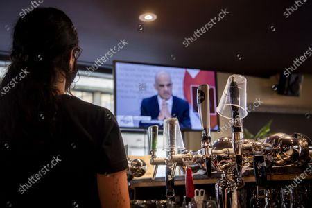 Bar staff watches Swiss Interior and Health Minister Alain Berset on a TV screen as he speaks during a press conference in Bern announcing new measures against the Coronavirus (COVID-19), inside of the bar-restaurant Les Boucaniers in Lausanne, Switzerland, 18 December 2020.