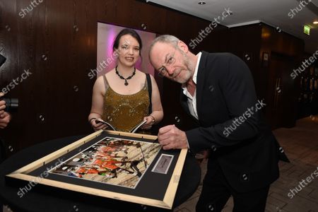 Liam Cunningham (IRL) signs his image with Caroline Reid (GBR) Formula Money. Zoom F1 Charity Auction & Reception, InterContinental London Park Lane, London, 16th January 2015. Sutton Images
