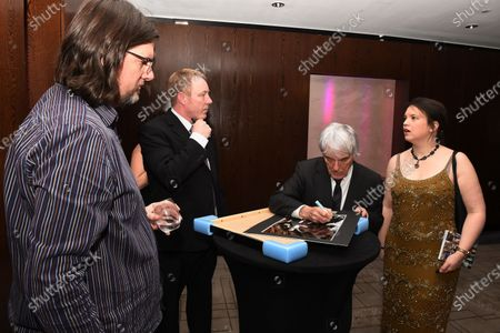 Bernie Ecclestone (GBR) CEO Formula One Group (FOM) signs his image with Caroline Reid (GBR) Formula Money and Steve D'Arcy (GBR) Arena Images. Zoom F1 Charity Auction & Reception, InterContinental London Park Lane, London, 16th January 2015. Sutton Images