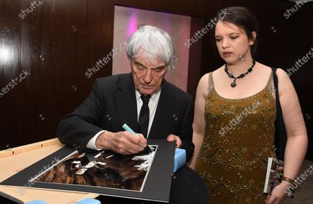 Bernie Ecclestone (GBR) CEO Formula One Group (FOM) signs his image with Caroline Reid (GBR) Formula Money. Zoom F1 Charity Auction & Reception, InterContinental London Park Lane, London, 16th January 2015. Sutton Images