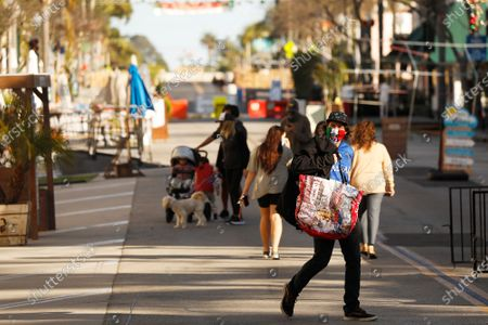 Stock Image of Ty Otto, right, walks the nearly empty East Main Street to pick up a take out order of food from a local restaurant where tables and chairs are stacked so they can not be used for patrons in downtown Ventura December 18, 2020 as Health officials in Ventura County say parties, indoor church services and youth sports events currently banned amid COVID-19 restrictions are continuing, hindering the county's ability to fight the spreading coronavirus. The county's intensive care unit capacity has dropped to 1%, and COVID-19 hospitalizations have broken records for 10 consecutive days. On Sunday, 181 COVID-19 patients were in the county's hospitals, 72% higher than the peak of the July surge. Ventura County on Thursday, Dec. 17, 2020 in Ventura, CA. (Al Seib / Los Angeles Times)