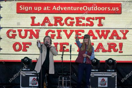 Stock Picture of Sen. Kelly Loeffler, R-Ga., right, and country music artist Travis Tritt draw the winner in a drawing for a gun during a campaign rally outside Adventure Outdoors gun store, in Smyrna, Ga