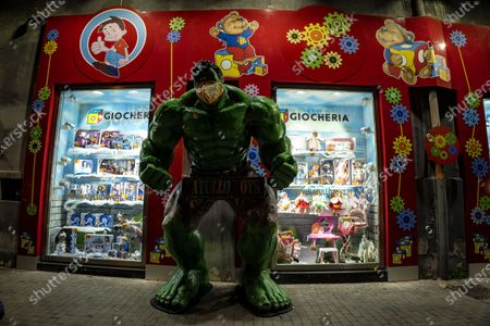 """Stock Picture of NAPLES, ITALY - DECEMBER 18, 2020 After the suspended coffee, Naples takes the field for families in difficulty with the """"Suspended Toy"""", designed for less fortunate children who, at Christmas, risk not finding a toy under the tree. A figure of the Marvel Comics Hulk character wearing a protective mask stands in front of a toy store in the city of Naples."""
