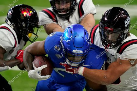 Buffalo running back Ron Cook Jr. (2) is tackled by Ball State's Tye Evans during the second half of the Mid-American Conference championship NCAA college football game, in Detroit