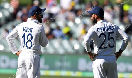 India's Virat Kohli, left, and Cheteshwar Pujara talk between deliveries to Australia on the third day of their cricket test match at the Adelaide Oval in Adelaide, Australia