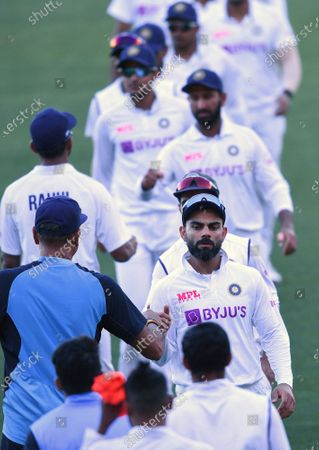 India's Virat Kohli, center right, shakes hands with coach Ravi Shastri following their loss to Australia on the third day of their cricket test match at the Adelaide Oval in Adelaide, Australia