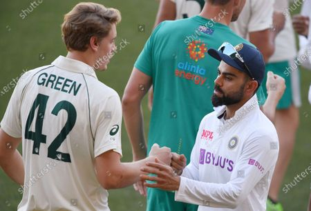 India's Virat Kohli, right, shakes hands with Australia's Cameron Green after Australia won on the third day of their cricket test match at the Adelaide Oval in Adelaide, Australia, . Australia won the match