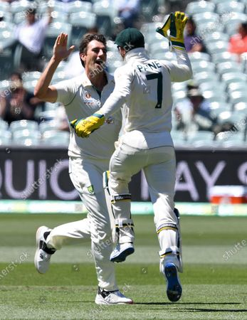 Australia's Pat Cummins, left, celebrates with his captain Tim Paine after the wicket of India's Virat Kohli on the third day of their cricket test match at the Adelaide Oval in Adelaide, Australia