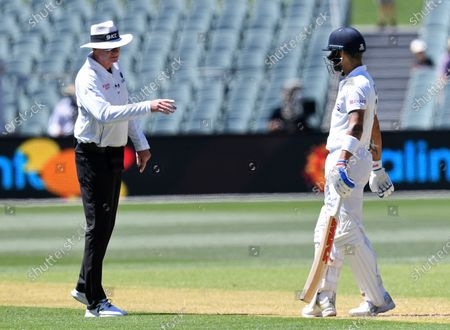 India's Virat Kohli, right, is held up by umpire Paul Reiffel as the third umpire checks the catch that takes Kohli's wicket for 4 runs against Australia on the third day of their cricket test match at the Adelaide Oval in Adelaide, Australia