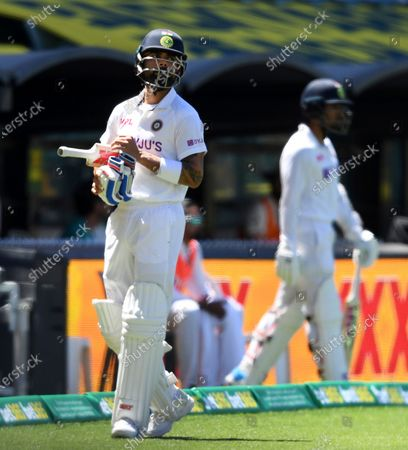 India's Virat Kohli, waits as he walks off as the third umpire checks the catch that takes Kohli's wicket for 4 runs against Australia on the third day of their cricket test match at the Adelaide Oval in Adelaide, Australia