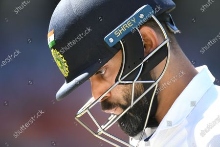 Indian captain Virat Kohli leaves the field after his dismissal by Australian bowler Pat Cummins for four runs during day three of the first Test Match between Australia and India at Adelaide Oval, Adelaide, Australia, 19 December 2020.