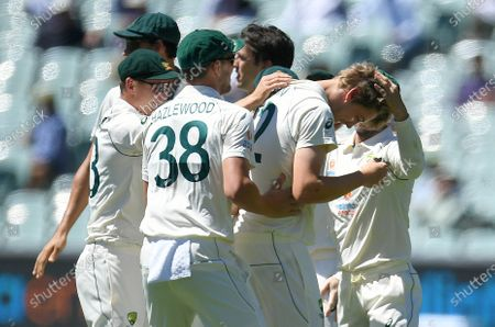 Australian players react with fielder Cameron Green (R) after he took a catch to dismiss Indian captain Virat Kohli for four runs during day three of the first Test Match between Australia and India at Adelaide Oval, Adelaide, Australia, 19 December 2020.