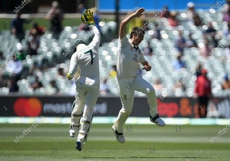 Australian bowler Pat Cummins reacts with captain Tim Paine (L) after dismissing Indian captain Virat Kohli  for four runs during day three of the first Test Match between Australia and India at Adelaide Oval, Adelaide, Australia, 19 December 2020.