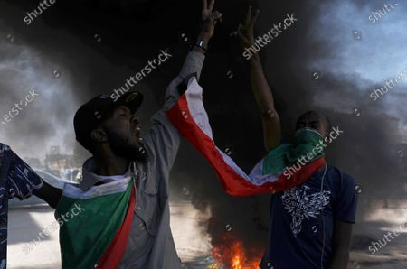 Demonstrator gives the victory sign during a protest, in Khartoum, Sudan, . Protests in Sudan's capital and across the country are demanding a faster pace to democratic reforms, in demonstrations that are marking the two-year anniversary of the uprising that led to the military's ouster of strongman Omar al-Bashir