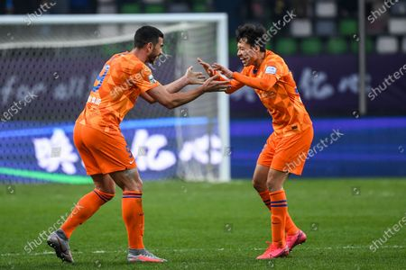 Graziano Pelle (L) of Shandong Luneng celebrates with teammate Song Long after the final match between Jiangsu Suning and Shandong Luneng at the CFA (The Chinese Football Association) Cup in Suzhou, east China's Jiangsu Province, Dec. 19, 2020.
