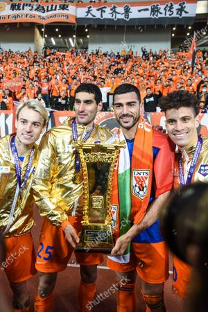 Shandong Luneng's Roger Guedes, Marouane Fellaini, Graziano Pelle and Moises Lima pose with the trophy after the awarding ceremony of the final match between Jiangsu Suning and Shandong Luneng at the CFA (The Chinese Football Association) Cup in Suzhou, east China's Jiangsu Province, Dec. 19, 2020.