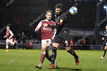 Lincoln City defender Lewis Montsma (4) heads the ball  under pressure from Northampton Town forward Danny Rose (29) during the EFL Sky Bet League 1 match between Northampton Town and Lincoln City at the PTS Academy Stadium, Northampton