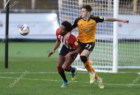 Lewis Collins of Newport County and Sido Jombati of Oldham Athletic compete for the ball
