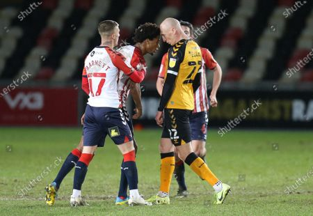Kevin Ellison of Newport County and Sido Jombati of Oldham Athletic are separated by team mates at the end of the match