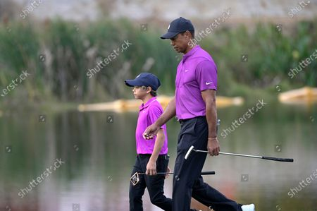 Tiger Woods, right, and his son Charlie walk together to the 16th green during the first round of the PNC Championship golf tournament, in Orlando, Fla