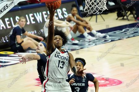 Connecticut guard Christyn Williams (13) drives to the basket against Xavier guards Aaliyah Dunham (3) and Lauren Wasylson (4) during the first half of an NCAA college basketball game, in Storrs, Conn