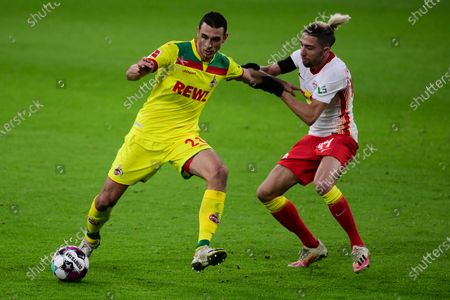 Kevin Kampl (R) of RB Leipzig competes for the ball with Ellyes Skhiri (L) of 1. FC Koeln during the German Bundesliga soccer match between RB Leipzig and 1. FC Cologne at Red Bull Arena in Leipzig, Germany, 19 December 2020.