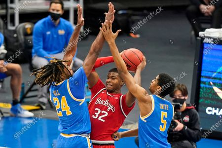 UCLA's Jalen Hill (24) and Chris Smith (5) put pressure on Ohio State's E.J. Liddell (32) in the first half of an NCAA college basketball game, in Cleveland