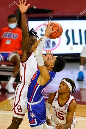 Houston Baptist guard Pedro Castro, center, shoots between Oklahoma forward Victor Iwuakor, left, and guard Alondes Williams (15) in the second half of an NCAA college basketball game, in Norman, Okla