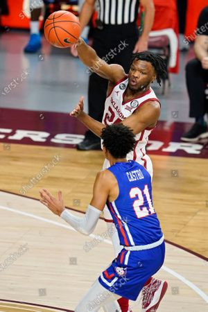 Oklahoma guard Elijah Harkless, top, passes over Houston Baptist guard Pedro Castro (21) in the first half of an NCAA college basketball game, in Norman, Okla