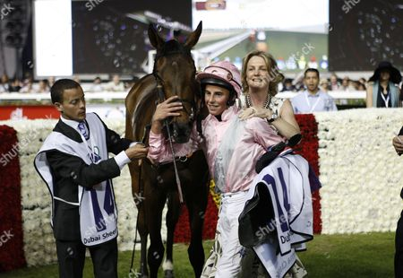 Jockey William Buick (C) and Madeleine Astrid Gurdon, Baroness Lloyd Webber, owner of Dar Re Mi from Britain, celebrate with her horce after winning the Dubai Sheema Classic race during the World Cup
