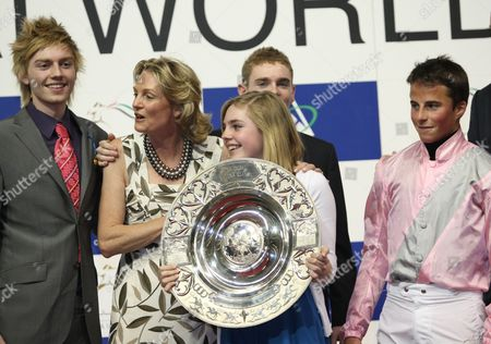 Stock Photo of Madeleine Astrid Gurdon, Baroness Lloyd Webber, owner of Dar Re Mi from Britain (2L) and William Buick, jockey (R), hold trophy with family after winning the Dubai Sheema Classic race
