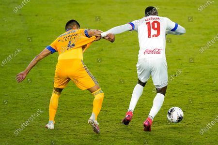 Stock Photo of Olimpia forward Yustin Arboleda (19) grabs the jersey of Tigres defender Hugo Ayala, left, to get position on the ball during the first half of a CONCACAF Champions League soccer match, in Orlando, Fla