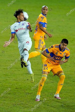 Olimpia defender Rodrigo Schlegel, left, gets a header in front of Tigres defender Hugo Ayala (4)during the second half of a CONCACAF Champions League soccer match, in Orlando, Fla