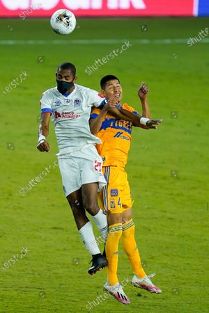 Olimpia forward Jerry Bengtson, left, and Tigres defender Hugo Ayala (4) go up for control of a head ball during the second half of a CONCACAF Champions League soccer match, in Orlando, Fla