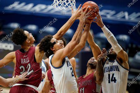 Villanova's Caleb Daniels (14) and Jeremiah Robinson-Earl (24) leap for a rebound against Saint Joseph's Rahmir Moore (11) and Jordan Hall (22) during the first half of an NCAA college basketball game, in Villanova, Pa