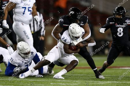 Stock Photo of Cincinnati defensive end Malik Vann (42) tackles Tulsa running back Corey Taylor II (24) as he carries the ball during the first half of the American Athletic Conference championship NCAA college football game, in Cincinnati