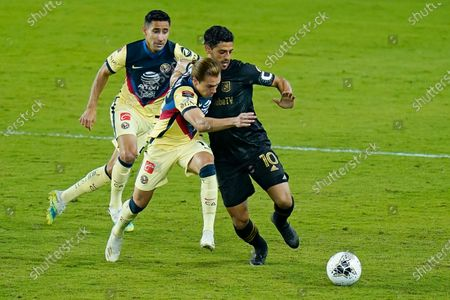 Stock Picture of Club America defender Luis Fuentes, left, and forward Sebastian Cordova, center, try to stop Los Angeles FC forward Carlos Vela (10) from advancing the ball during the first half of a CONCACAF Champions League soccer match, in Orlando, Fla