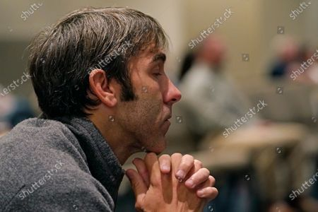Matthew Chambers clasps his hands in prayer during services at Highland Colony Baptist Church in Ridgeland, Miss., . The church practices covid protocols by allowing families to sit spaced out from others, separating older and more vulnerable members in the Worship Center and providing sanitizer and masks at the entrance