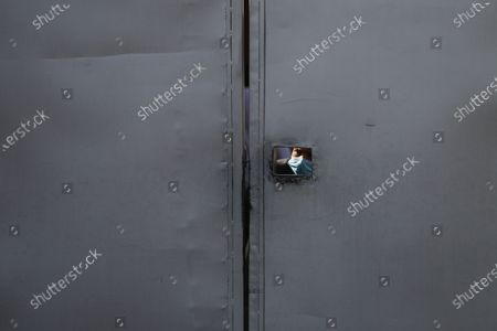 A security personnel looks through the peephole of a gate at the Prime Minister's residence in Kathmandu, Nepal, 20 December 2020. According to media reports, Nepalese Prime Minister K.P. Sharma Oli, in response to challenge from party rivals, recommended the dissolution of the Parliament and called for general election during an emergency Cabinet meeting held on the day. The decision has been ratified by President Bidhya Devi Bhandari, who has called a two-phase election to be held in April and May 2021, media added.
