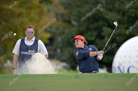 Little John Daly, right, son of golfer John Daly, hits out of a bunker onto the 18th green during the final round of the PNC Championship golf tournament, in Orlando, Fla