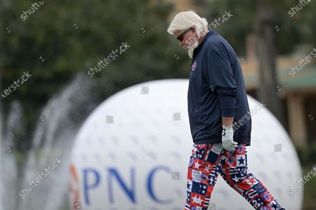 John Daly walks to his ball on the 18th green during the final round of the PNC Championship golf tournament, in Orlando, Fla