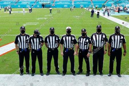 The NFL officials left to right: referee Daniel Gallagher (85), field judge Jimmy Russell (82), down judge Danny Short (113), referee Brad Allen (122), field judge Rick Patterson (15), umpire Bruce Stritesky (102) and side judge Boris Cheek (41), stand on the field before an NFL football game between the Miami Dolphins and the New England Patriots, in Miami Gardens, Fla
