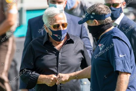 New England Patriots owner Robert Kraft and New England Patriots Head Coach Bill Belichick wear masks as they bump fists on the sidelines before the Patriots take on the Miami Dolphins during an NFL football game, in Miami Gardens, Fla
