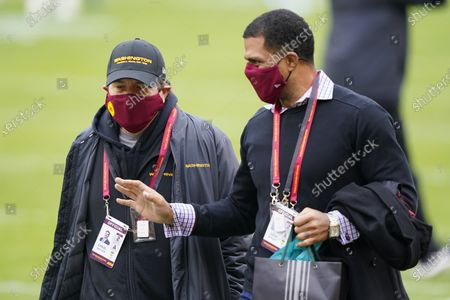 Washington Football Team owner Dan Snyder, left, walking on the field with Team President Jason Wright, right, before the start of an NFL football game against the Seattle Seahawks, in Landover, Md