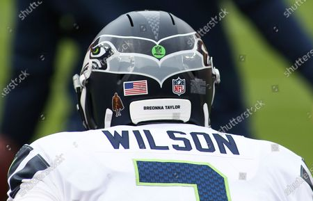 """Seattle Seahawks quarterback Russell Wilson (3) dons a helmet sticker as a Walter Payton Man of The Year nominee and says """"Breonna Taylor"""" before an NFL football game against the Washington Football Team, in Landover, Md"""
