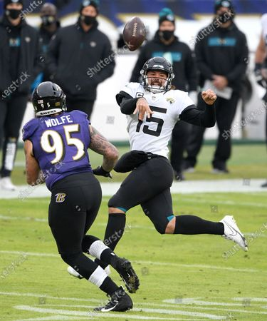 Jacksonville Jaguars quarterback Gardner Minshew II (15) throws a pass as Baltimore Ravens defensive end Derek Wolfe (95) applies pressure during the second half of an NFL football game, in Baltimore