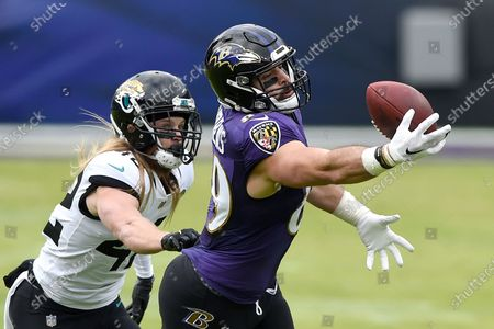 Baltimore Ravens tight end Mark Andrews (89) reaches but is unable to catch a pass from quarterback Lamar Jackson, not visible, as Jacksonville Jaguars safety Andrew Wingard (42) defends during the first half of an NFL football game, in Baltimore