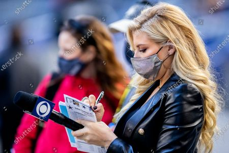 Sideline reporter Melanie Collins writes down a note before an NFL football game between the San Francisco 49ers and Dallas Cowboys, in Arlington, Texas. Dallas won 41-33
