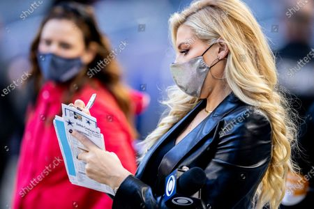 Stock Image of Sideline reporter Melanie Collins writes down a note before an NFL football game between the San Francisco 49ers and Dallas Cowboys, in Arlington, Texas. Dallas won 41-33